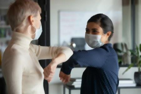 Due donne con mascherina si salutano col gomito, immagine sfocata Covid