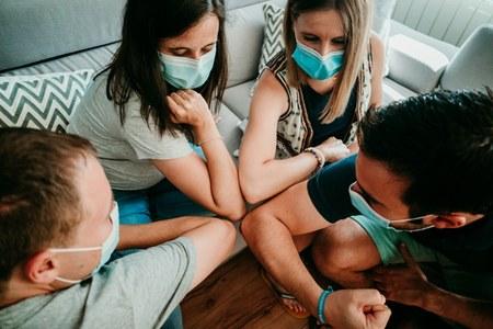 Giovani con mascherina si salutano col gomito, Covid, ragazzi, ragazze