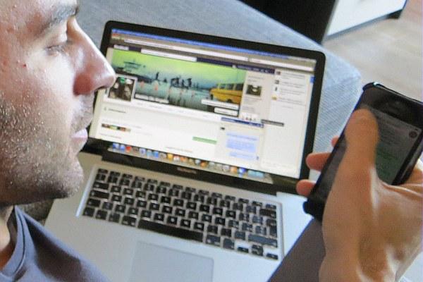 Ragazzo al computer con lo smartphone