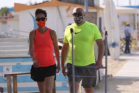 Covid, coppia in spiaggia, mascherina