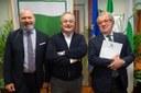 I presidenti Bonaccini e Maroni con al centro il sottosegretario Bressa davanti al gonfalone